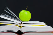 Stack of books with green apple and clean blackboard — Stock Photo