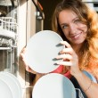 Young woman putting dishes in the dishwasher  — Foto de Stock