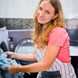 Housework: young woman doing laundry (shallow DOF) — Stock Photo #32695657