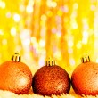 Yellow christmas balls on white fur and  colorful lights  — Stock Photo