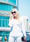 Beautiful young blond woman talk by phone outdoor — Stock Photo
