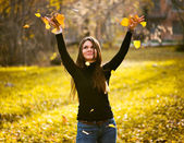 Young woman throwing leaves woman in the forest — Stock Photo