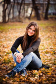 Young woman sits on leaves in autumn park — Stock Photo
