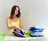 Mujer hermosa joven feliz planchado de ropa. — Foto de Stock