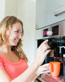 Happy woman making coffee cup machine kitchen interior — Stock Photo