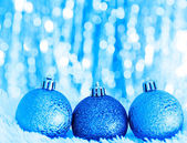 Blue christmas balls on white fur and lights — Stock Photo