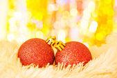 Bolas de navidad amarillas en pieles blancas y luces de colores — Foto de Stock