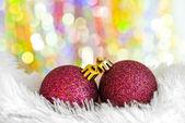 Christmas balls on white fur and colorful lights — Stock Photo
