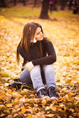 Beautiful thoughtful girl in autumn park — Stock Photo