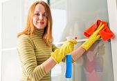 Girl wiping the dust from wooden furniture at home — Stock Photo