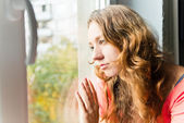 Beautiful young woman is sad at the window — Stock Photo