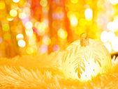 Yellow christmas balls on white fur and colorful lights — Stock Photo