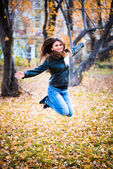 Girl in the black jacket jumps in the park in autumn — Stock Photo