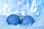 Blue christmas balls on white fur and lights — Stock Photo