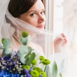 Young beautiful bride waits for groom near the window — Stock Photo #34306185
