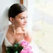 Young beautiful bride waits for groom near the window — Stock Photo #34306373