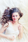 Brown-haired woman lying on her duvet in her bedroom — Stock Photo