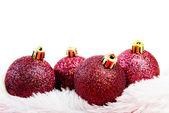 Four red Christmas ball on white fur — Stock Photo