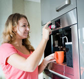 Happy young woman making coffee cup machine kitchen interior — Stock Photo