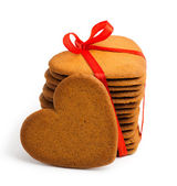 Heart shaped sugarcookie tied with red ribbon — Stock Photo