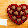 Chocolate pralines in red heart shape box on table — Stock Photo #39093045