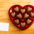 Chocolate pralines in red heart shape box on table — Stock Photo