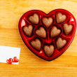 Chocolate pralines in red heart shape box on table — Stock Photo #39093105