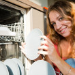 Young woman putting dishes in the dishwasher — Stock Photo