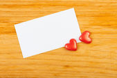Red hearts and note on wooden background — Stock Photo