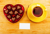 Chocolate pralines in red heart shape box on table — Foto de Stock