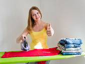 Young beautiful woman ironing clothes in room — Stock Photo