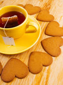 Cup with tea bag and heart-shaped cookies — Stockfoto