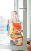 Happy young woman housewife washes a window — Stock Photo