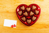 Chocolate pralines in red heart shape box on table — Foto Stock