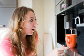 Shock young woman making coffee cup machine kitchen interior — Stock Photo