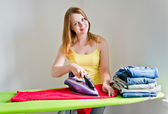 Happy young beautiful woman ironing clothes. Housework — Stock Photo