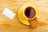 Cup with tea bag and heart-shaped cookies — Stock Photo
