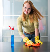 Happy girl cleaning table with furniture polish at home — Stock fotografie