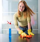 Szczęśliwa dziewczyna czyszczenia tabeli meble z polski w domu — Zdjęcie stockowe