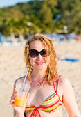 Young woman with fruit cocktail relaxing on beach  — Stock Photo