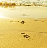 波と砂の足跡 — ストック写真