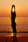 silhouette of young woman in sea on sunset   — Stock Photo
