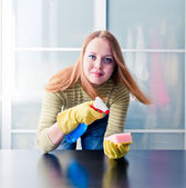 Happy girl cleaning table — Stock Photo