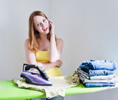 Housewife talking on the phone while ironing — Stock Photo