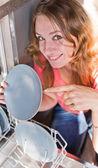 Mujer poniendo platos en el lavavajillas — Foto de Stock