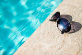 Sunglasses near swimming pool — Stock Photo