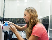 Woman employee pouring detergent in washer — Stock Photo