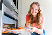 Beautiful woman putting meat into oven — Stock Photo