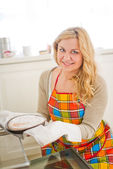 Woman pulling pie from oven — Stock Photo