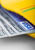 US dollars bills and Visa credit card in wallet. — Stock Photo
